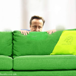 David Cameron hides behind green sofs